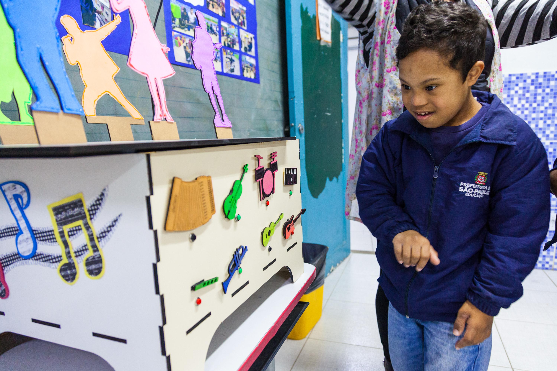 Em sala aula, estudante observa a Caixa de Instrumentos Musicais, apoiada em carteira escolar. O aluno está sendo supervisionado por professora. Fim da descrição.