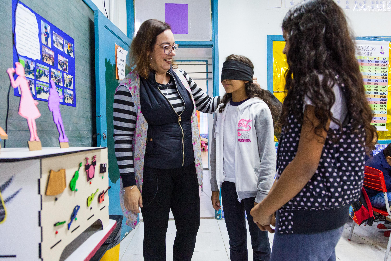 Em sala de aula, duas estudantes interagem com a Caixa de instrumentos musicais. Uma delas está vendada e a professora a orienta com a mão esquerda sobre o seu ombro. Fim da descrição.