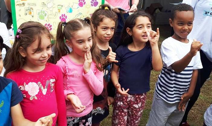 Seis crianças em pé e perfiladas (4 meninas e 2 meninos) fazem gestos em Libras com as mãos. Fim da descrição.