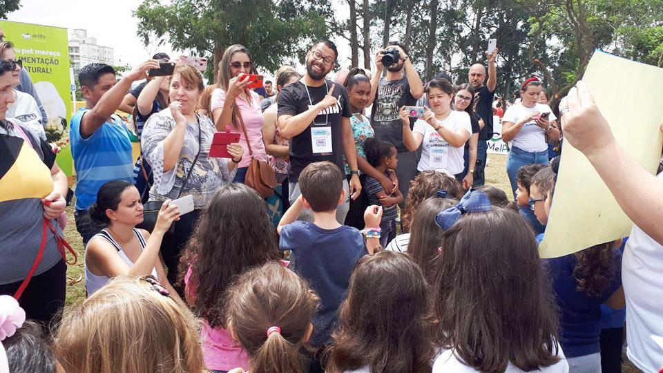 Ao redor de crianças, professor Diogo conversa em Libras, enquanto pessoas observam e tiram fotos. Ao fundo, existem árvores. Fim da descrição.