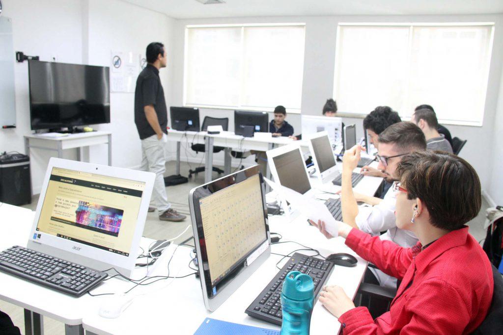 Em sala de informática, estudantes sentados em cadeiras trabalham em computadores atentos em professor, que está de pé no centro da sala. Fim da descrição.