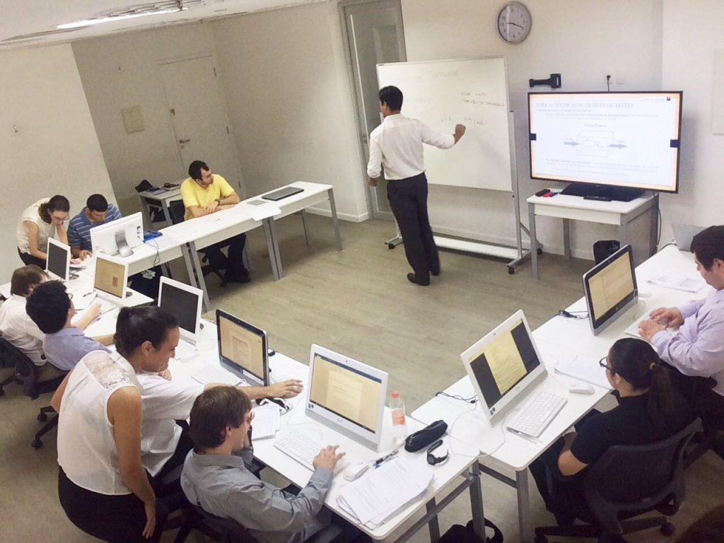 Em sala de informática, estudantes sentados em cadeiras trabalham em computadores atentos em professor, que, em pé, escreve em lousa branca. Fim da descrição.