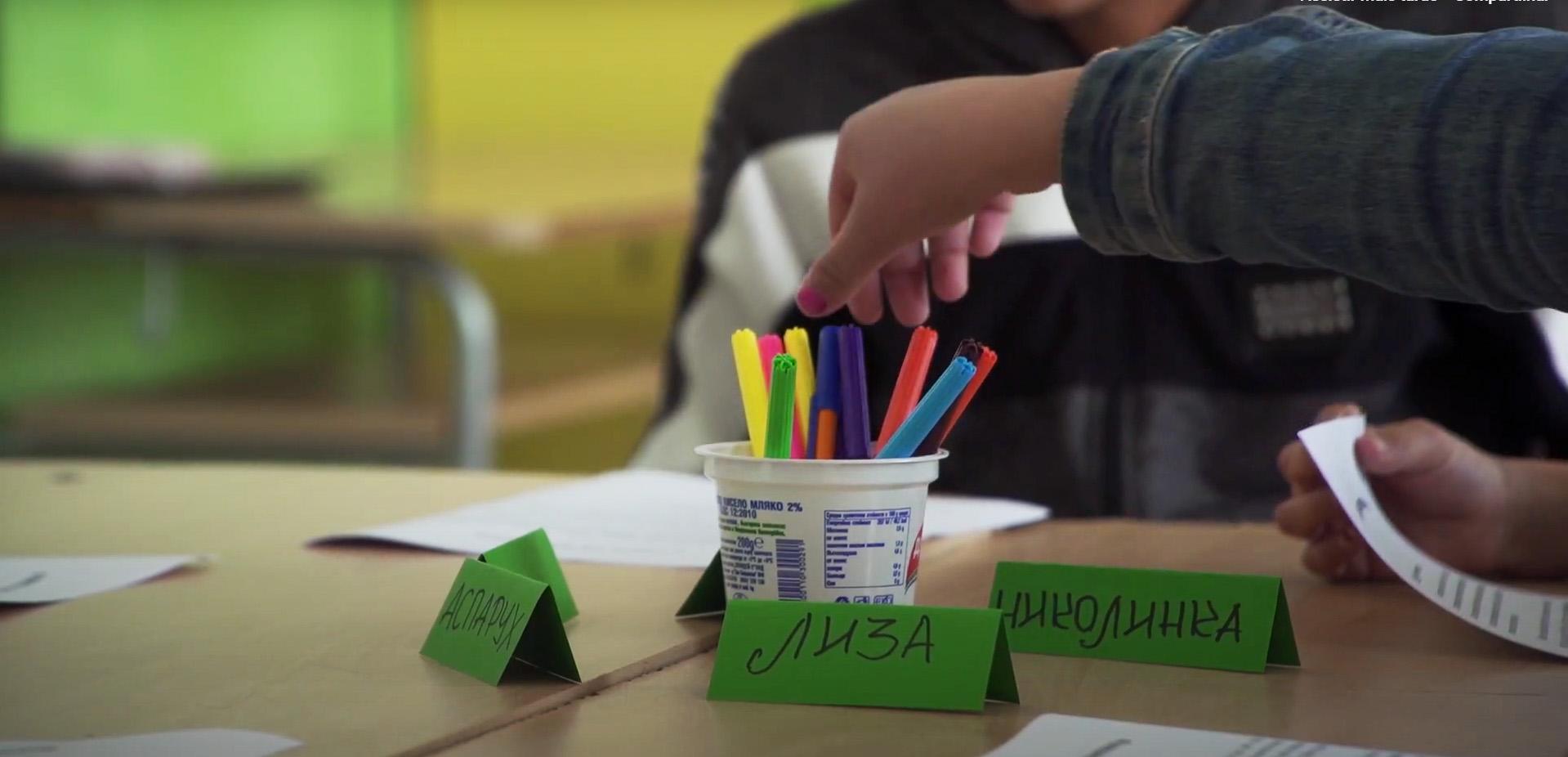 Em sala de aula de escola, estudante escolhe canetinha colorida de copo em cima da mesa. Ao redor do copo, plaquinhas com nomes em búlgaro. Fim da descrição.