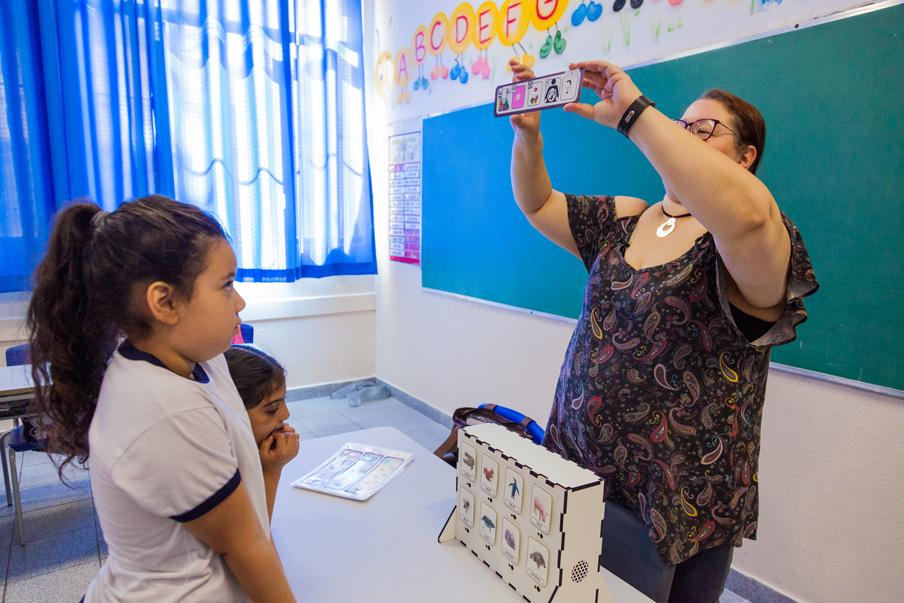 Em sala de aula, o painel de adivinhação está sobre a mesa, enquanto a professora apresenta parte do material para a sala e duas alunas prestam atenção. Fim da descrição.