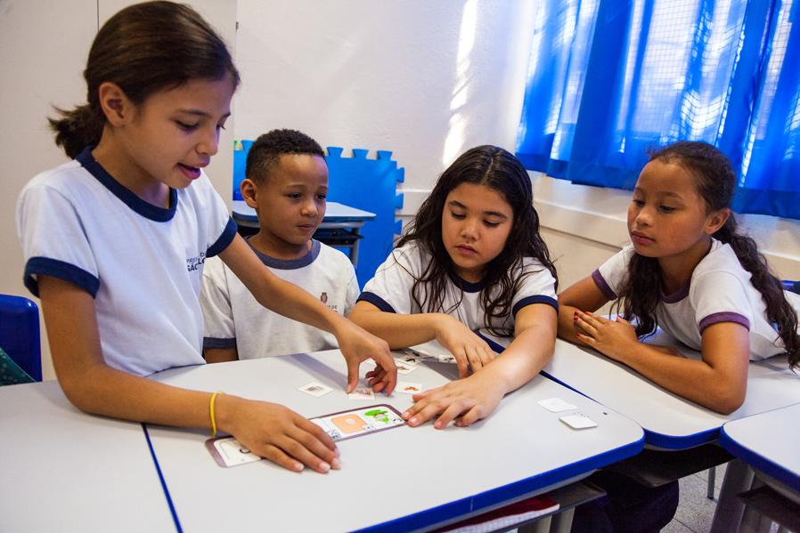 Em torno de uma mesa, quatro estudantes interagem com as figuras de animais do material pedagógico. Fim da descrição.