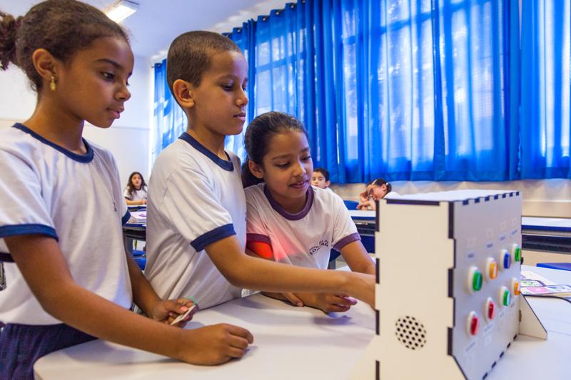 O Painel de adivinhação está em cima da mesa, enquanto dois estudantes apertam seus botões e, com uma figura na mão, outra aluna observa. Fim da descrição.