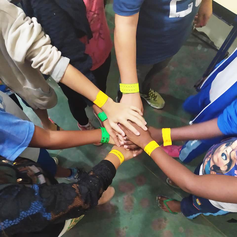 Em sala de aula, sete estudantes juntam as mãos no centro de uma roda. Dois estão com pulseiras VIP verdes no pulso, enquanto os outros usam pulseiras VIP amarelas. Fim da descrição.
