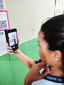 Em sala de aula, aluna aponta o celular para acessar QR Code de painel criado no projeto. Fim da descição.