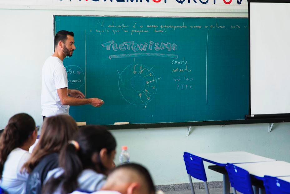 """Em sala de aula, professor está ao lado da lousa. Nela, está escrito: """"Tectonismo"""", acima de um desenho do planeta Terra, com as legendas """"crosta, """"manto"""", """"núcleo"""" e """"nite"""". Fim da descrição."""