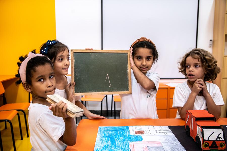 Em sala de aula, quatro estudantes estão em volta do Caminho sustentável. Duas alunas levantam uma lousa com o número um escrito e seus dois colegas observam. Fim da descrição.
