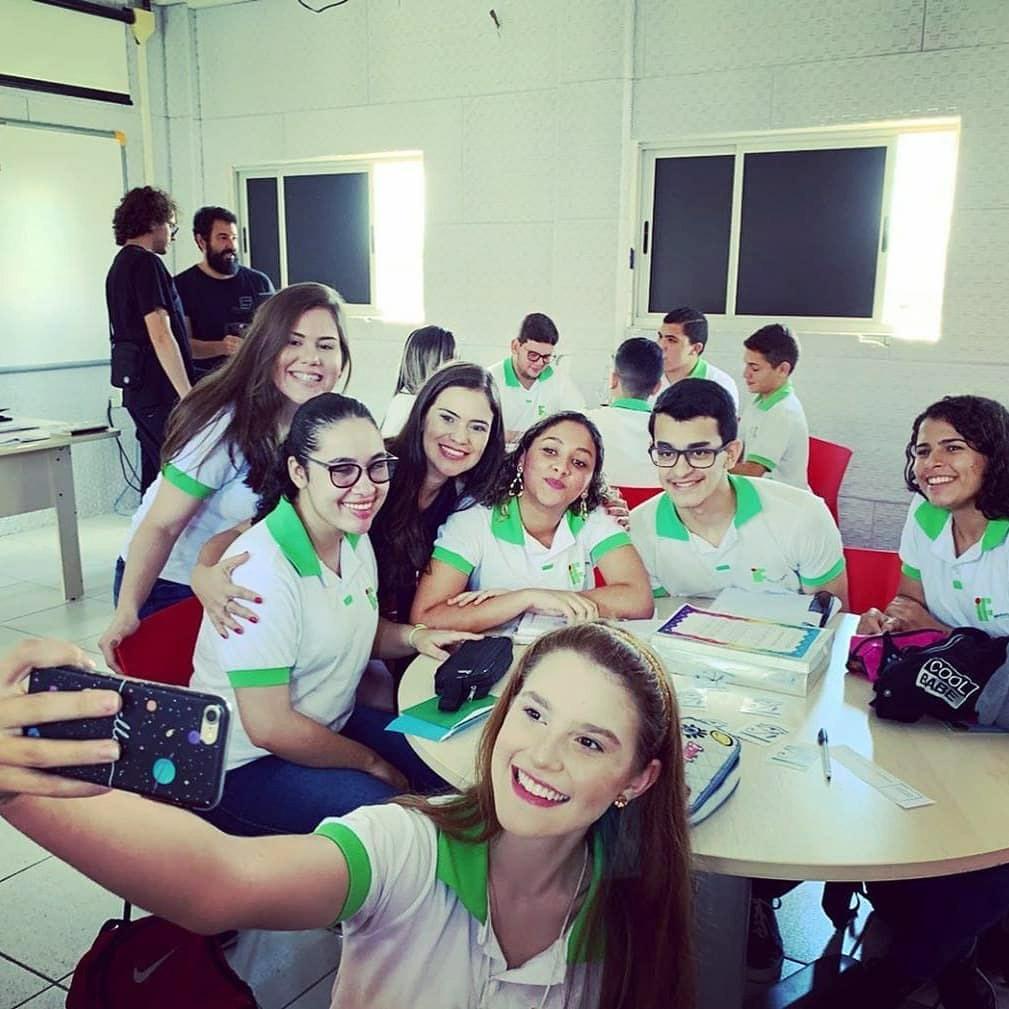 Em sala de aula e ao redor de mesa circular, estudantes posam para selfie abraçados com professora Patrícia. Sobre a mesa materiais do jogo da argumentação, cadernos e estojos. Ao fundo, outros estudantes se reúnem ao redor de mesa. Fim da descrição