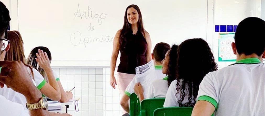 """Em sala de aula, estudantes sentados em carteiras escolares observam professora Patrícia. Ela está em pé, de frente para os alunos, e de costas para uma lousa em que está escrito """"Artigo de opinião"""". Fim da descrição."""