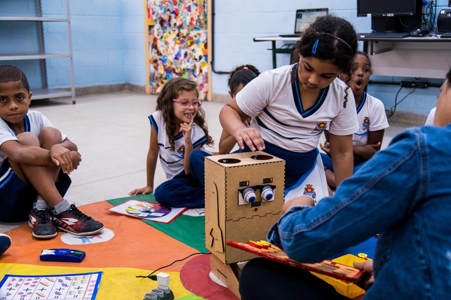 Com colegas observando em volta e supervisão da professora, aluna insere fichas na cabeça do Arizinho. Fim da descrição.