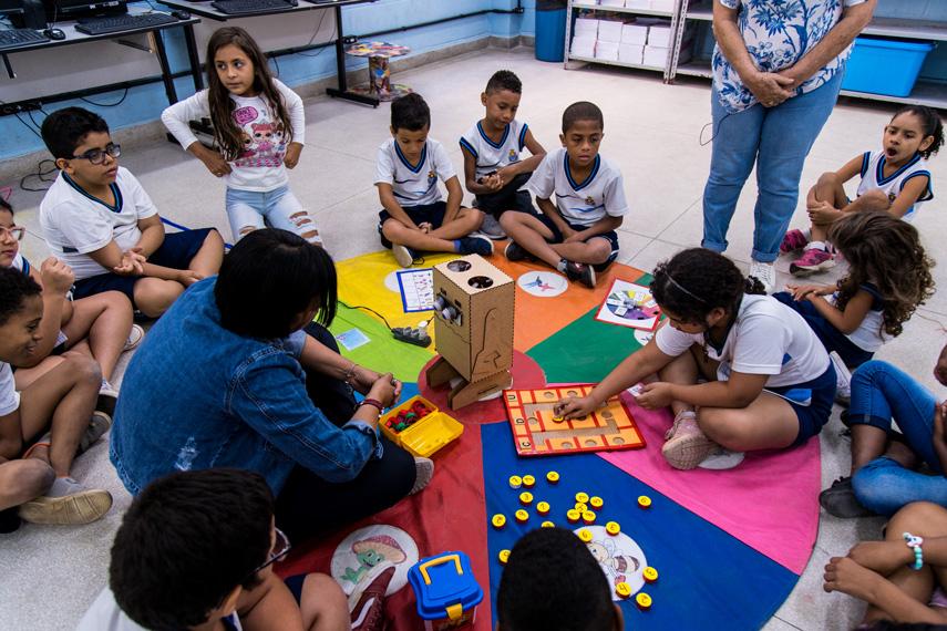 Em sala de aula, estudantes e educadora estão sentados em volta do material pedagógico acessível. Fim da descrição.