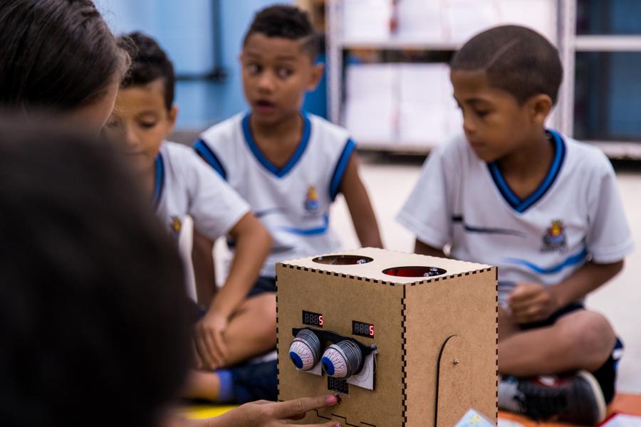 Em sala de aula, estudante aperta botão do robô Arizinho, que mostra o número 5. Demais estudantes observam ao fundo. Fim da descrição.