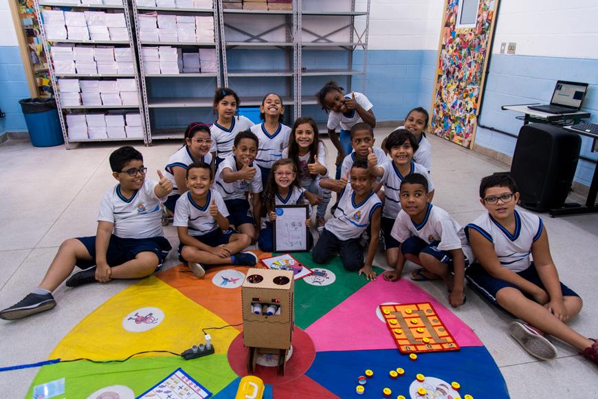 Em sala de aula, toda a turma está sentada no chão. Posam para a foto em volta de tapete colorido, com Arizinho no centro. Fim da descrição.
