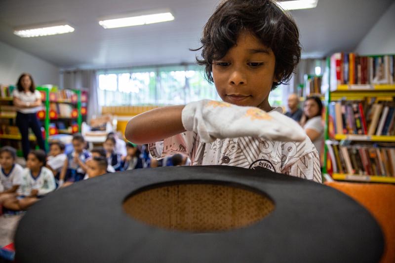 Em sala de leitura, estudante passa a mão com uma luva sobre a Cartola mágica. Ao fundo, estudantes o observam sentados no chão ao lado de prateleiras de livros. Fim da descrição.