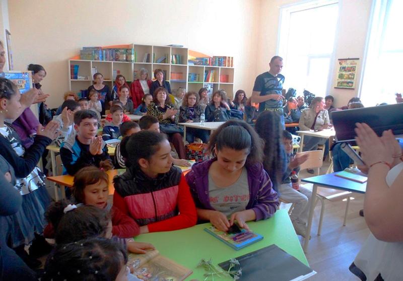 Estudantes e familiares estão em uma sala de aula, alguns sentados, outros em pé. Algumas pessoas aplaudem. Fim da descrição.
