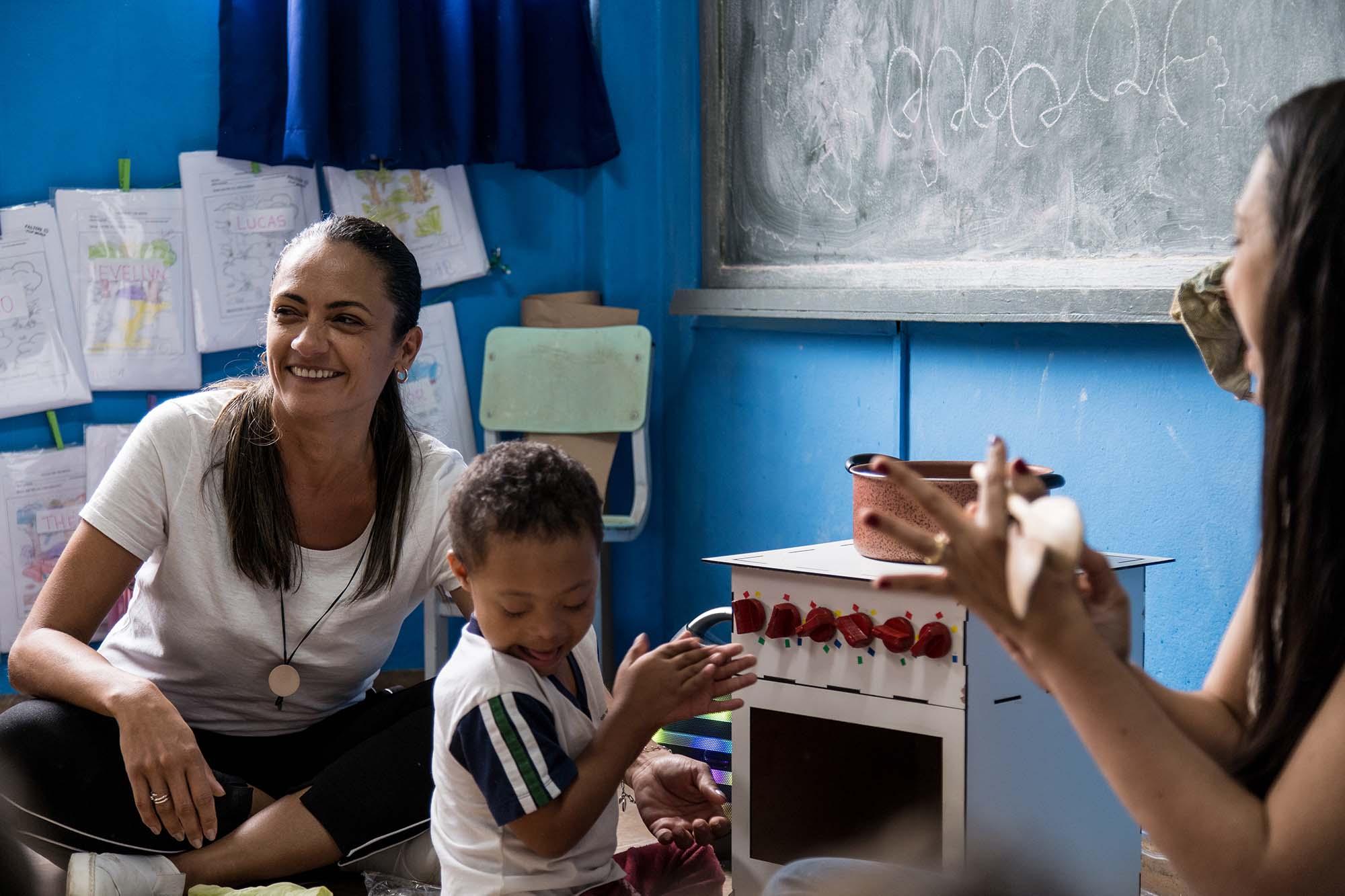 Em sala de aula, de frente para o fogão musical, estudante com Síndrome de Down e professores batem palmas. Fim da descrição.