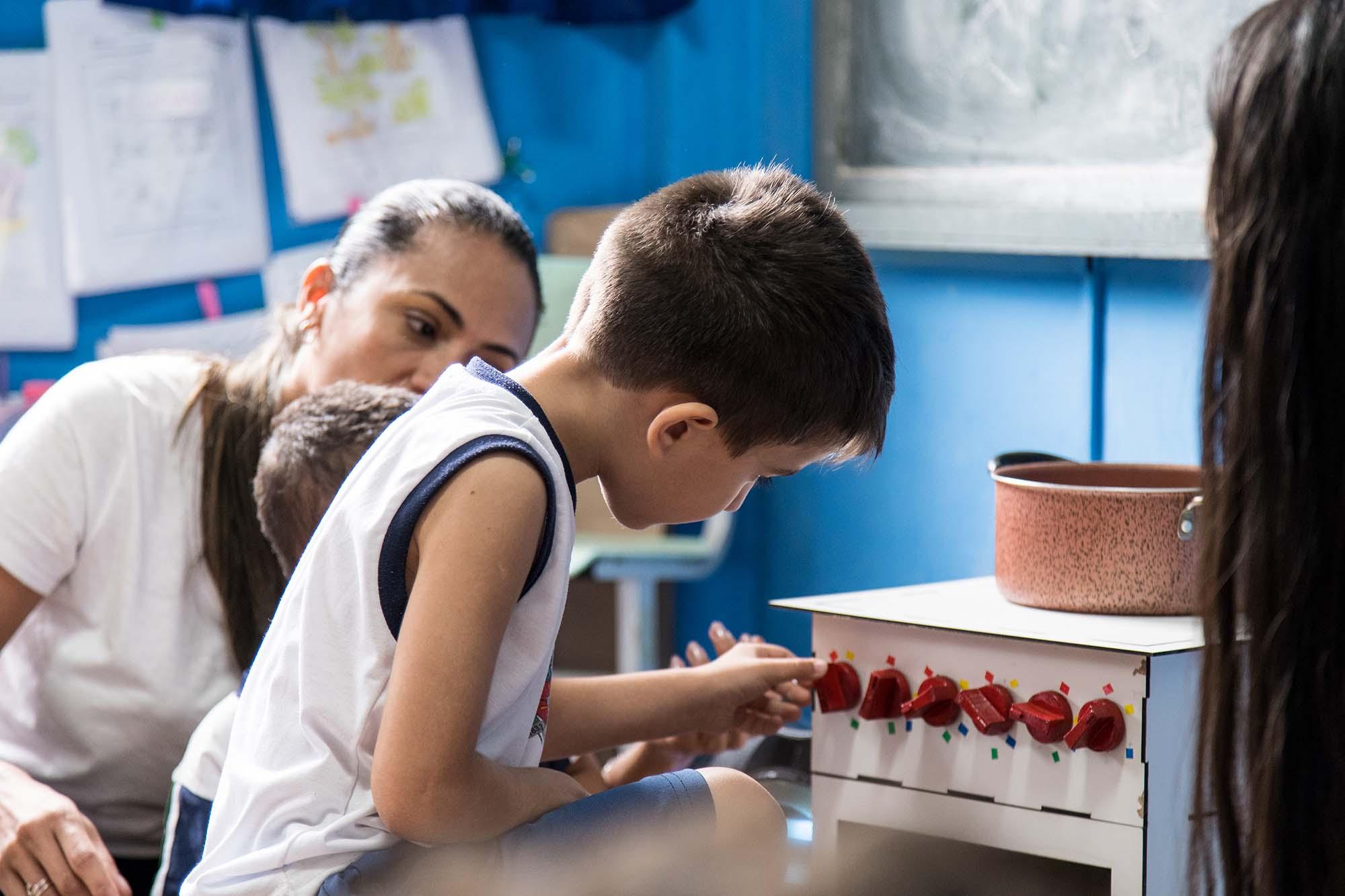 Em sala de aula, aluno manuseia um dos botões do fogão musical, enquanto é observado por professora. Fim da descrição.