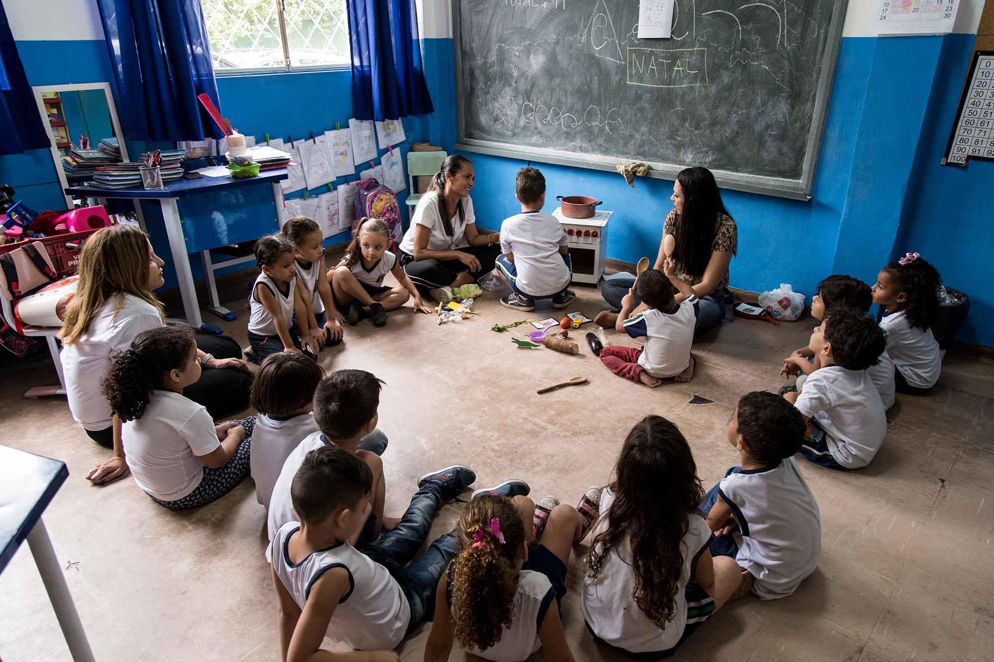 Em sala de aula, estudantes em roda sentados no chão observam aluno manuseando fogão musical, enquanto duas professoras supervisionam a atividade. Fim da descrição.