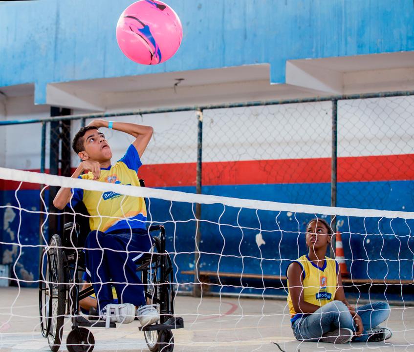 Em quadra escolar, estudante em cadeira de rodas prepara movimento de saque com bola no ar, enquanto é observado por aluna sentada no chão. Há uma rede de vôlei em frente a eles em uma altura mais baixa que o usual. Fim da descrição.