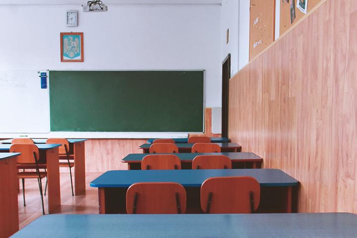 Em sala de aula, carteiras de estudantes vazias. Ao fundo lousa verde contrasta com parede branca. Fim da descrição.
