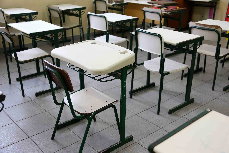 Sala de aula com carteiras de estudantes vazias. Fim da descrição