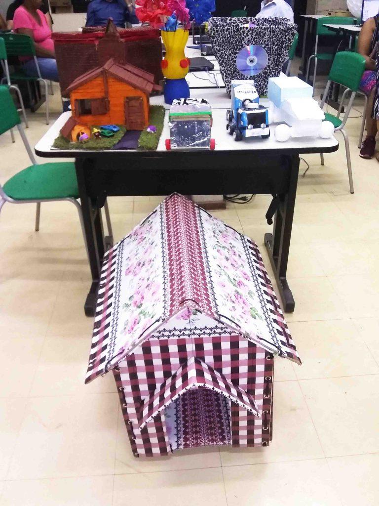 Projetos em exposição. Em cima de mesa, uma casa, carrinhos e objetos construídos com materiais recicláveis. No chão, uma casa para animais domésticos. Fim da descrição.