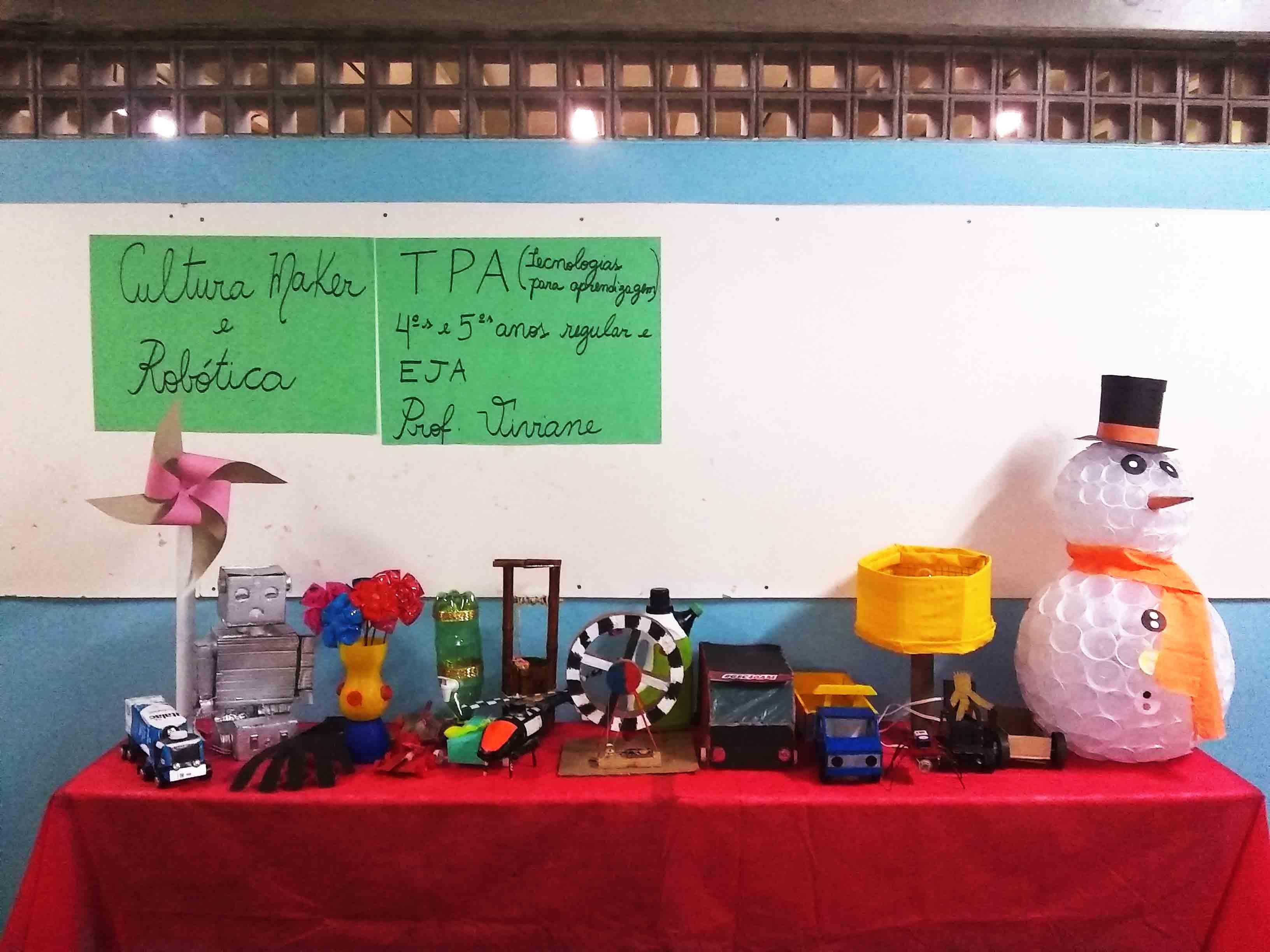 """Projetos em exposição. Sobre mesas escolares há um robô, caminhões, um boneco de neve, um catavento, um helicópetro e outros objetos construídos pelos estudantes. Na parede, dois cartazes em papel verde escrito """"Cultura Maker e Robótica"""" e """"TPA (Tecnologia para aprendizagem) quartos e quintos anos regular e EJA. Prof. Viviane"""". Fim da descrição."""