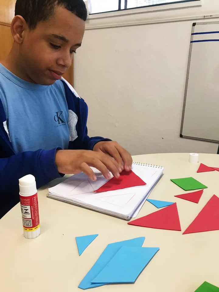 Estudante Diogo Bonfim, vestindo blusa e jaqueta azuis, posiciona triângulo de EVA vermelho em caderno de desenho. Sobre a mesa, estão losangos e outros triângulos vermelhos, azuis e verdes e cola bastão. Fim da descrição.