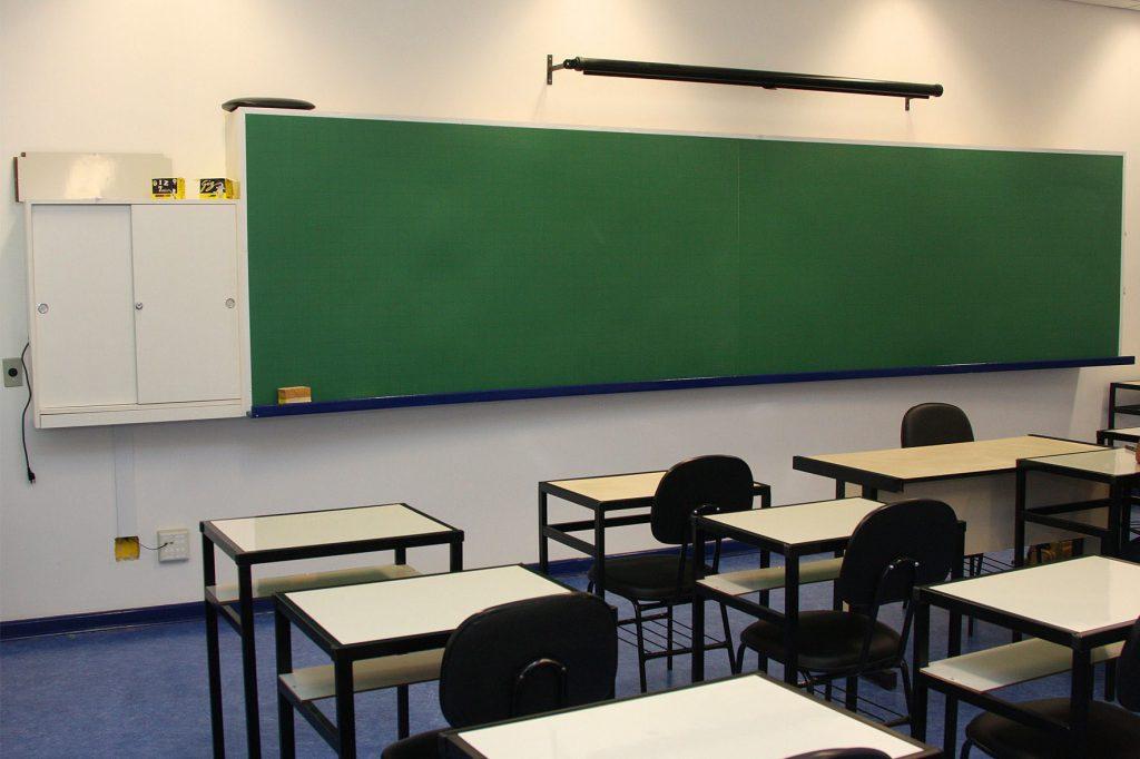 Em sala de aula, carteiras de estudantes vazias. Ao fundo, lousa verde. Fim da descrição.