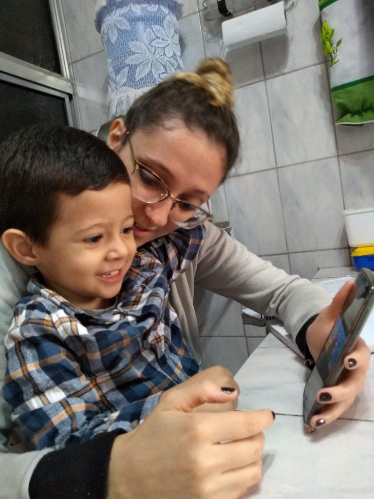 Em cozinha, sentada em mesa, mulher segura criança em seu colo. Ela apoia em sua mãe um aparelho celular, que é observado pela criança. Fim da descrição.