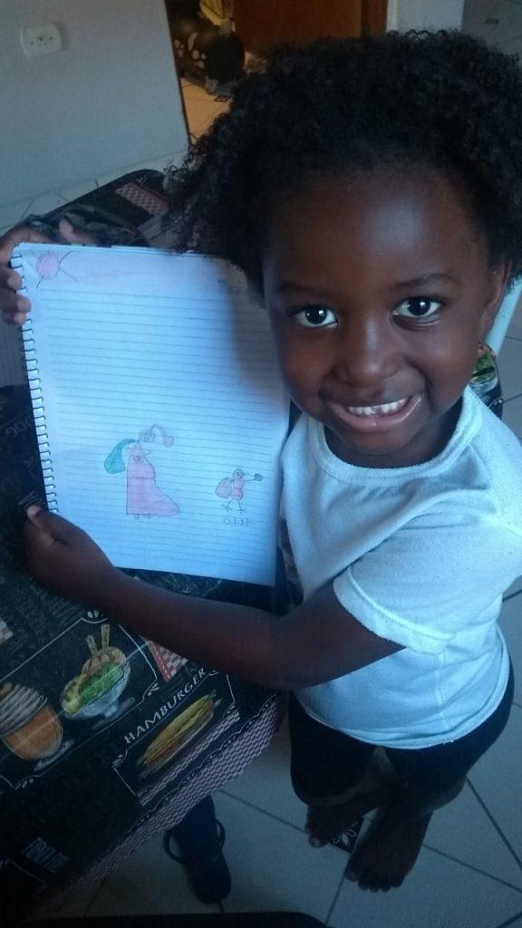Criança sorri enquanto expõe caderno com desenhos feitos à mão. Fim da descrição.