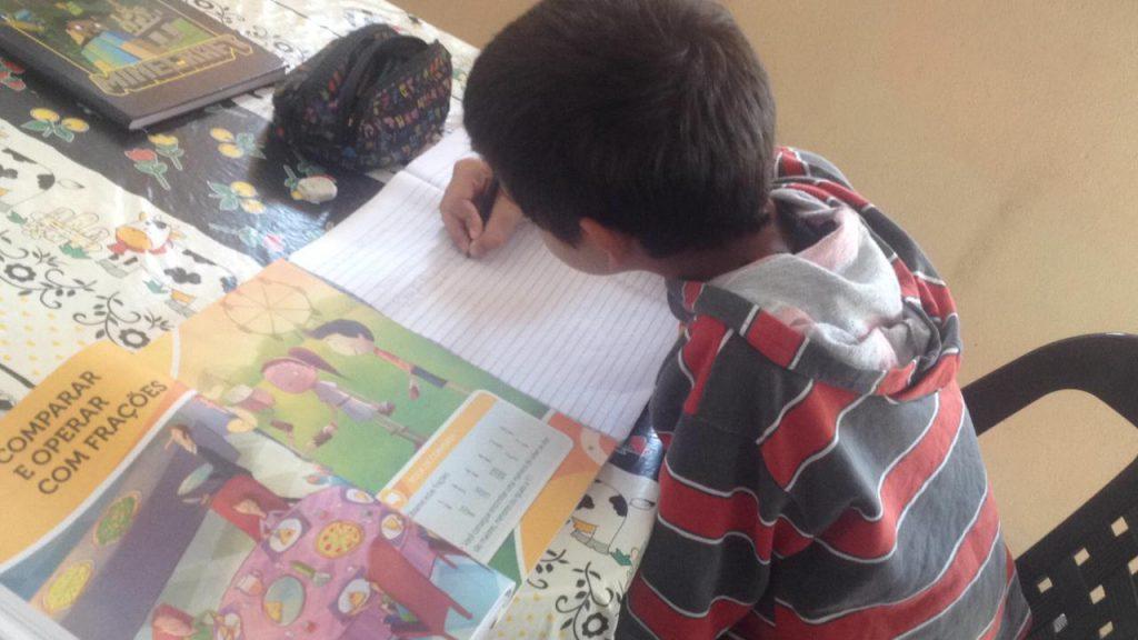 Sobre mesa, estudante escreve em caderno ao lado de livro e estojo escolar. Fim da descrição.