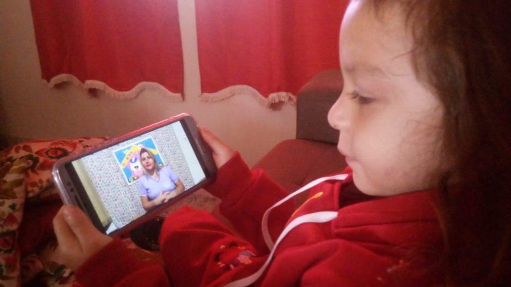 Sentada em sofá de casa, criança assiste, em celular apoiado em suas mãos, a aula. Fim da descrição.
