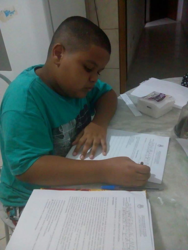 Criança faz exercícios em folha de papel sobre mesa. Fim da descrição.