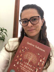 """Denise posa para foto com o livro """"Longe da árvore"""" de Andrew Solomon. A capa traz ilustrações de pessoas diversas e Denise usa óculos e uma blusa branca. Fim da descrição."""