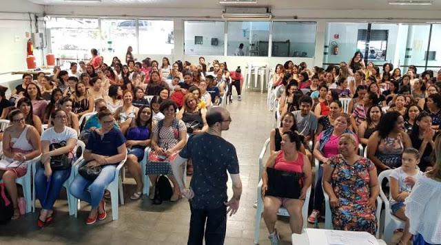 Emílio Figueira de pé e de costas para a câmera, diante de uma grande plateia de pessoas sentadas. Fim da descrição.