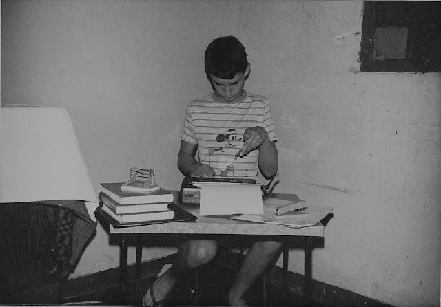 Foto em preto e branco de Emílio Figueira aos nove anos, sentado em sua primeira mesinha de trabalho, datilografando em uma máquina de escrever portátil. Fim da descrição.