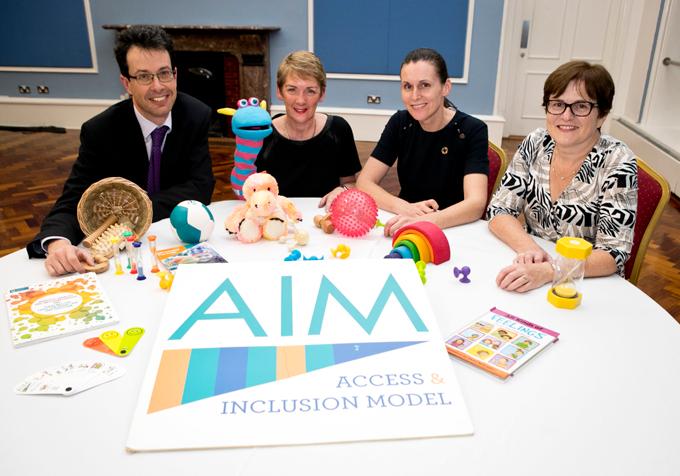 """Em volta de mesa circular, três mulheres e um homens (membros do governo irlandês) posam para foto. Sobre a mesa livros. brinquedos e bichos de pelúcia. Ao centro, banner do modelo em que se lê: """"AIM: Acess and Inclusion Model"""". Fim da descrição."""