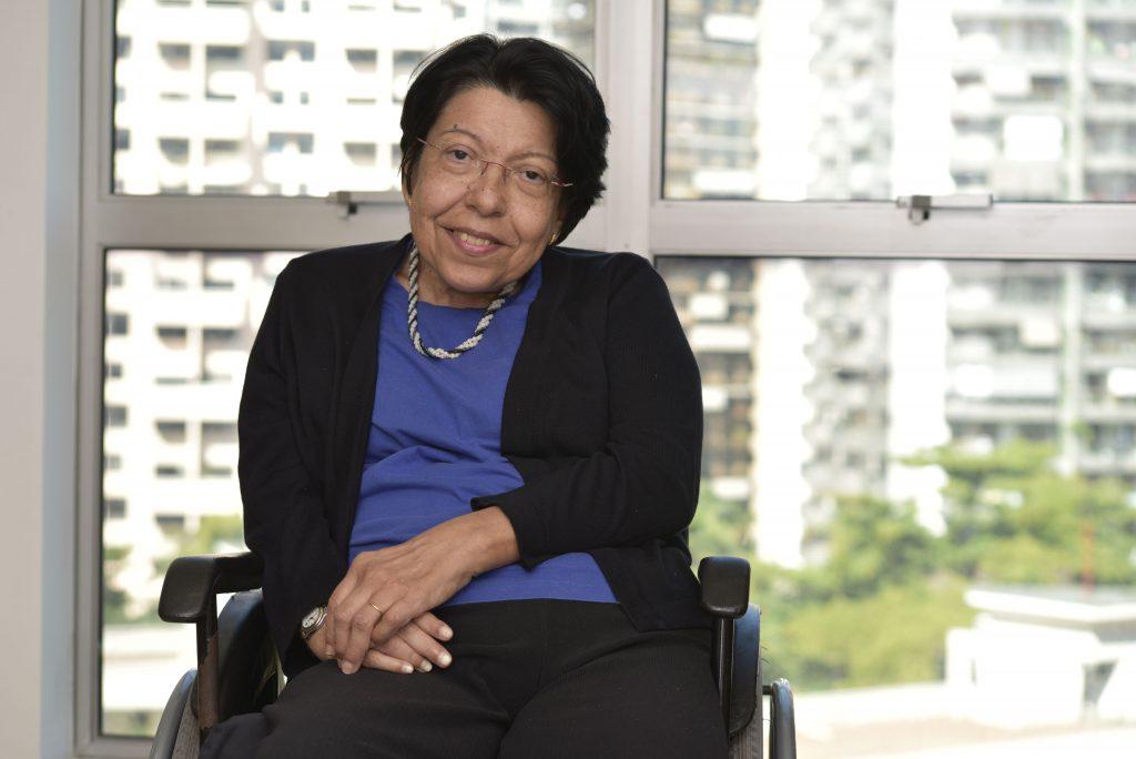 Izabel Maior, sentada em cadeira de rodas e com uma mão apoiada sobre a outra, posa para foto sorridente. Fim da descrição.