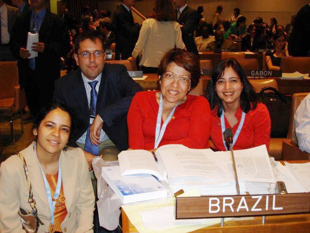 """Em plenário da ONU em Nova York, quatro componentes da delegação brasileira posam para foto. Ao centro Izabel Maior está em cadeira de rodas e na mesa em sua frente estão depositados livros abertos. Em frente aos livros uma placa em que se lê """"Brazil"""". Fim da descrição."""