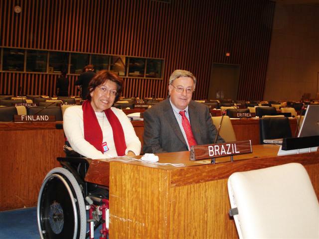"""Em plenário da ONU, Izabel Maior, em cadeira de rodas, e Don MacKay, presidente do Comitê de Elaboração da Convenção, posam para foto atrás de mesa do plenário, sobre a qual uma placa em que se lê """"Brazil"""". Fim da descrição"""