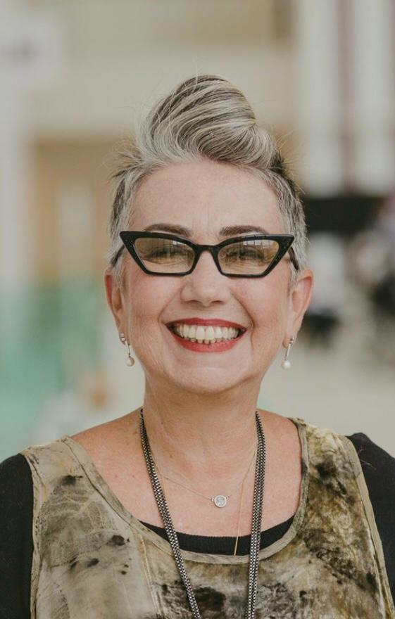 Imagem de Claudia Wernerck. Ela é uma mulher na faixa dos 50 anos, com cabelos grisalhos. Ela sorri e utiliza óculos com lentes amarelas, brincos e colar. Fim da descrição