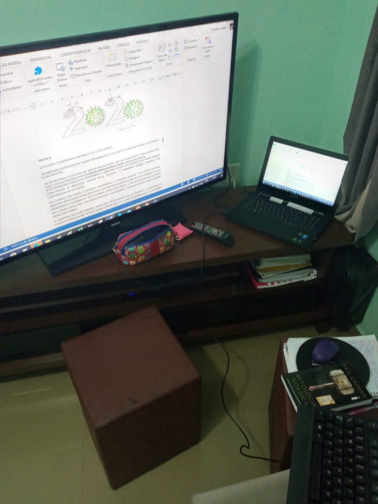 Em sala de estar, Gislaine grava viídeos em Livras senada em cadeira. Ao seu redor, estão aparelhos utilizados para a gravação, como televisão, computdaor, teclado, aparelho celular e livro. Fim da descrição.