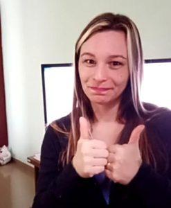 Em sala de estar e em frente à TV, Gislaine faz sinal de positivo com as duas mãos. Fim da descrição.