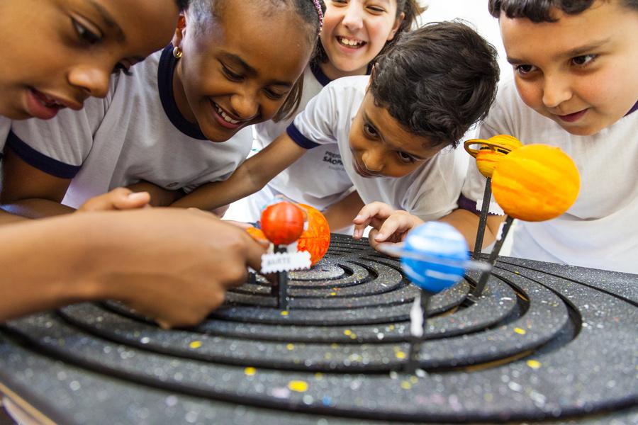 """Em sala de aula, estudantes interagem com planetas do material pedagógico acessível """"Sistema Solar interativo"""". Fim da descrição."""