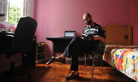 Emílio ao centro da imagem, sentado de pernas cruzadas em cadeira no seu quarto, enquanto lê livro. Fim da descrição.
