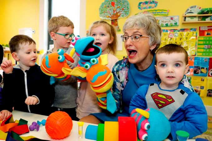 Em sala com brinquedos e materiais didáticos, professora vesta fantoches interagindo com quatro crianças. Fim da descrição